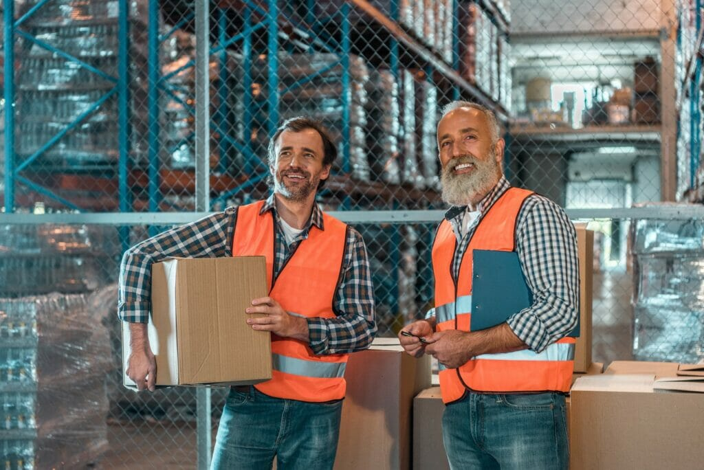 smiling workers with clipboard and box working together in warehouse